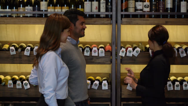 customer couple asking for a wine suggestion to female sommelier at a wine cellar who helps them very cheerfully - wine bar stock videos & royalty-free footage