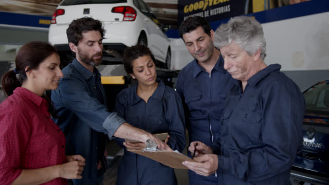 customer couple talking to team of mechanics at an auto repair shop while supervisor looks at a list on clipboard - jumpsuit stock videos & royalty-free footage