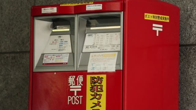 stockvideo's en b-roll-footage met a customer drops a letter in a post box at the shinjuku post office operated by japan post holdings co in tokyo japan on monday sept 11 the japanese... - postkantoor
