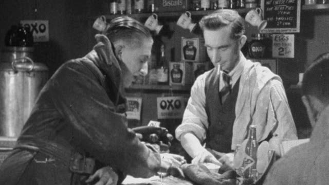 1930 montage customer enters a pub, chats with the publican, and sits with his friends / united kingdom - 1930点の映像素材/bロール