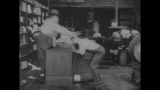 1917 customer (buster keaton) expects clerk (fatty arbuckle) to retrieve money from molasses and ends up with a sticky hat - 1917 stock-videos und b-roll-filmmaterial