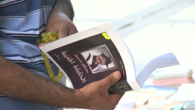 customer flipping through book in outdoor market / baghdad, iraq - libro in brossura video stock e b–roll