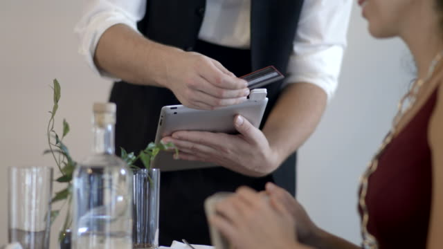 CU LA Customer gives waiter a payment card, he swipes card on digital tablet at the table and turns it to woman to sign.