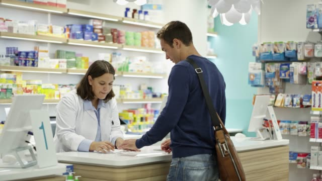 customer giving prescription to chemist at store - pharmacy stock videos & royalty-free footage