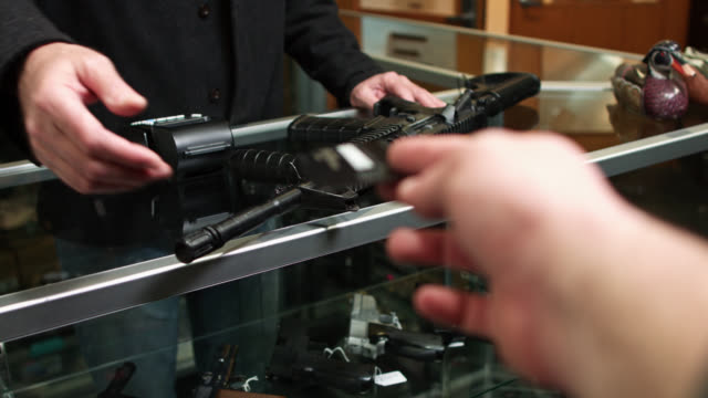 customer handing over credit card in exchange for assault rifle in gun store - arma da fuoco video stock e b–roll
