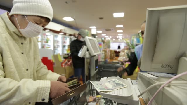 vídeos de stock e filmes b-roll de customer hands over japanese 1,000 yen banknotes while making a purchase at a checkout counter of a sankei super, k.k. supermarket in tokyo, japan,... - making money