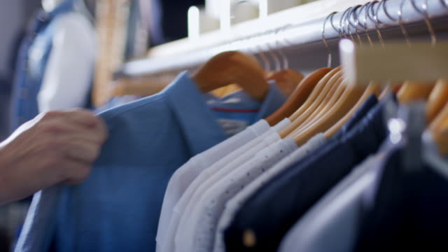 vídeos de stock, filmes e b-roll de customer hangs shirt back on rack in modern clothing store - mercadoria