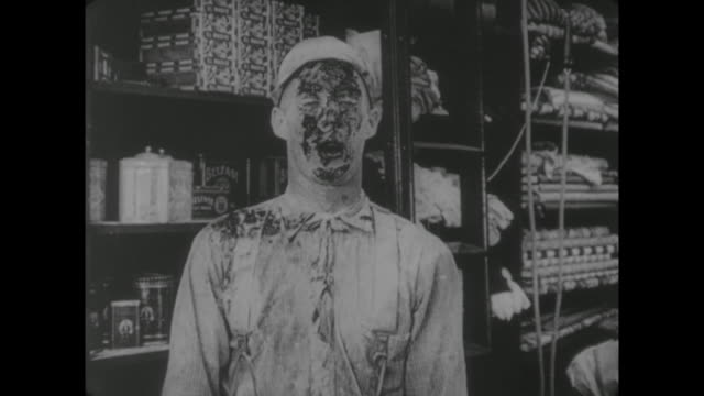vídeos de stock e filmes b-roll de 1917 customer (buster keaton) hits dazed store clerk (al st. john) in face with fruit pie - pie humano