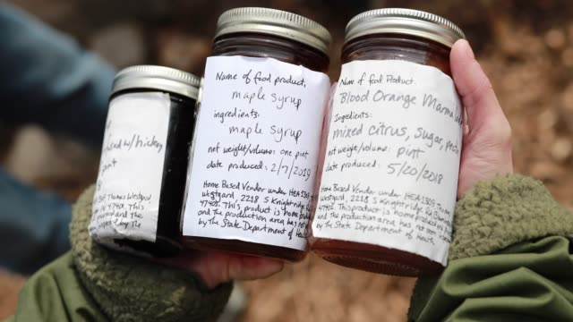 a customer holds jars of homemade wood fired maple syrup and jar of homemade marmalade at the knightridge farmstand sunday march 10 2019 in... - maple syrup stock videos & royalty-free footage