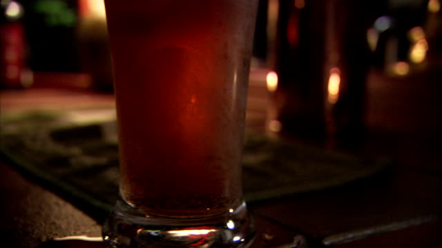 A customer in a pub sets a pint glass full of ale on the bar. Available in HD.