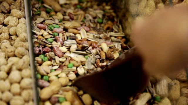 customer in the shop takes nuts mix from the box - nut food stock videos & royalty-free footage