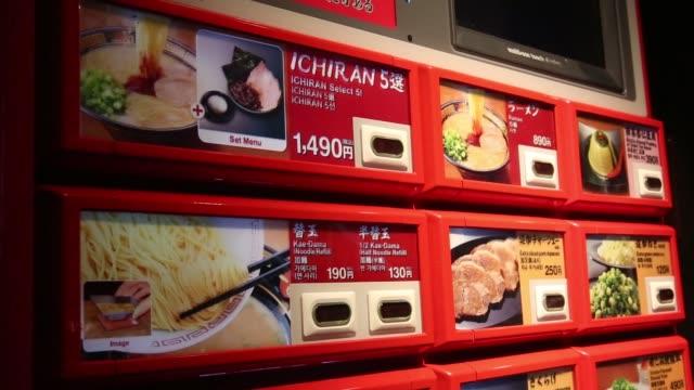 a customer is greeted by an employee and enters an ichiran inc tonkots ramen restaurant in fukuoka japan on dec 22 customers eat tonkotsu ramen at an... - ramen noodles stock videos & royalty-free footage
