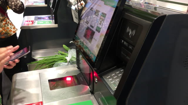 vidéos et rushes de customer is paying with mobile phone on self-service cashier in supermarket. in china, more and more supermarkets are equipped with the self-service... - paiement mobile