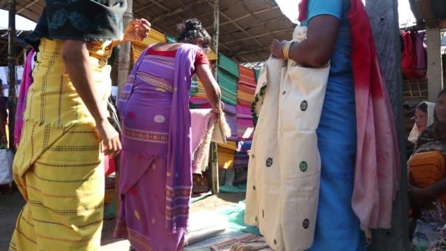 A customer left inspects a silk fabric as merchants look on at a market in Udalgudi Assam Customers browse silk fabrics on sale at a market in...