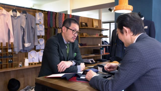 Customer looking at fabric swatches with a tailor