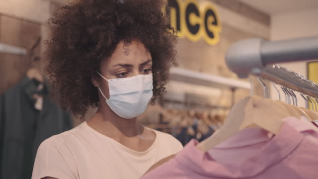 customer looking at vintage clothes in shop wearing protective face mask during coronavirus pandemic - solo ragazze video stock e b–roll