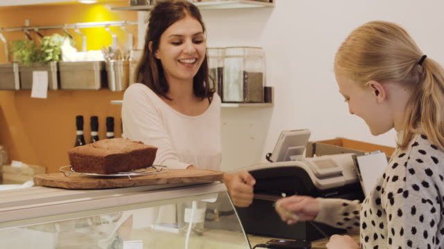 Customer makes contactless payment on card reader in cafe.