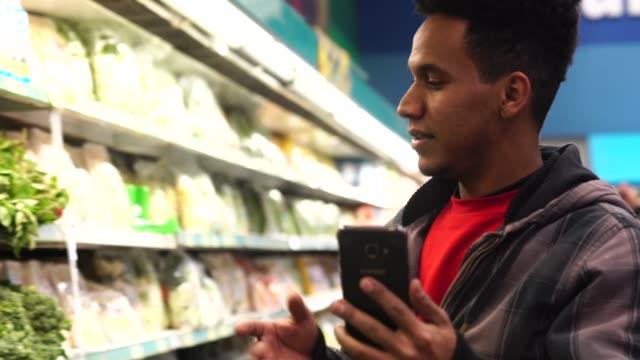 vidéos et rushes de client de faire un chat vidéo au supermarché - société de consommation