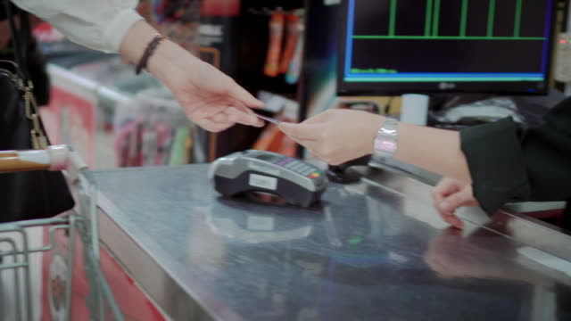 Customer making contactless payment with credit card at supermarket checkout