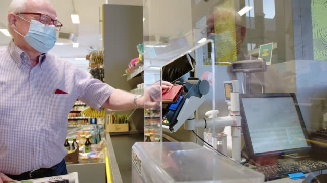 customer making nfc mobile payment at grocery store - prevention stock videos & royalty-free footage