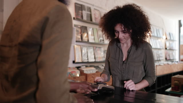 Customer making payment with smartphone in a record store