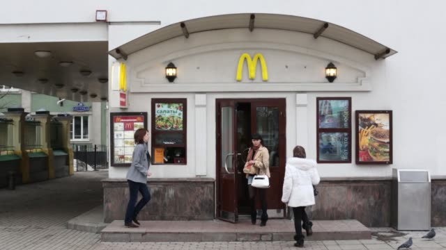 a customer orders his meal from a service window outside a mcdonald food restaurant in moscow customers enter and exit a mcdonald food restaurant in... - mcdonald's stock-videos und b-roll-filmmaterial