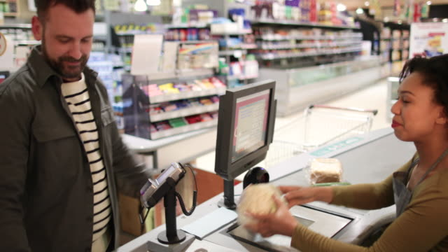 Customer paying for groceries at till