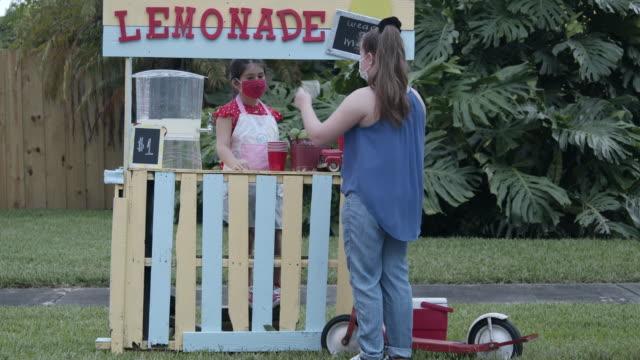 vídeos de stock e filmes b-roll de customer paying for her lemonade - vender