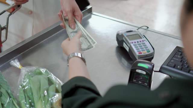 Customer paying for shopping at supermarket checkout,Over shoulder shot