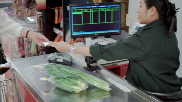 customer paying for shopping at supermarket checkout,steadicam shot - cashier stock videos and b-roll footage