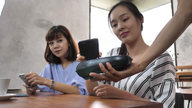 vídeos de stock, filmes e b-roll de cliente pagar com pagamento sem contacto de telefone inteligente no cafe - pagamento móvel