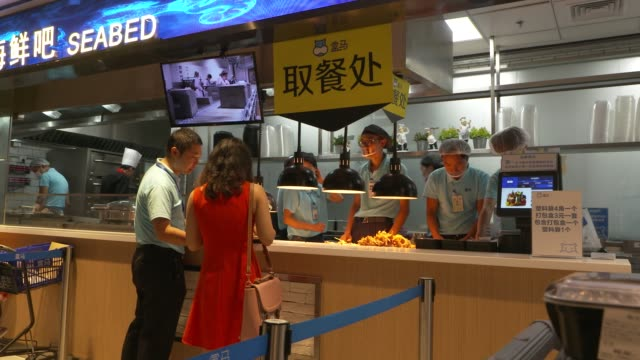 A customer picks up a cooked food order at a restaurant inside an Alibaba Group Holding Ltd Hema Store in Shanghai China on Tuesday Sept 12 Customers...