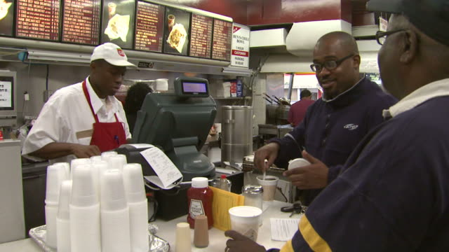 customer placing order at ben's chili bowl while another stirs a cup of coffee / washington, district of columbia, united states - five people stock videos & royalty-free footage