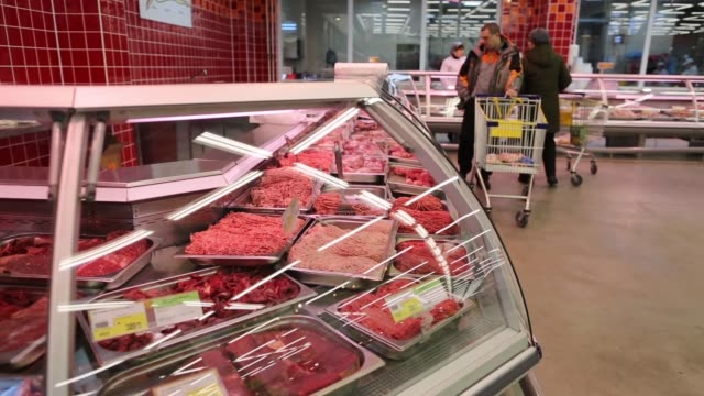 A customer pushes a trolley past the fresh meat counter inside a Lenta LLC supermarket in Prokopyevsk Kemerevo region Russia An employee serves a...