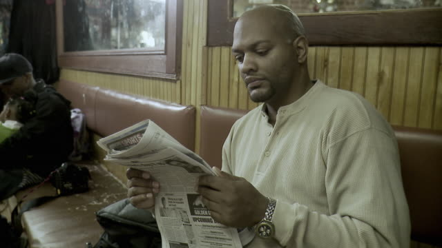 ms customer reading newspaper while waiting at barbershop, brooklyn, new york city, new york state, usa - see other clips from this shoot 1437 stock videos and b-roll footage