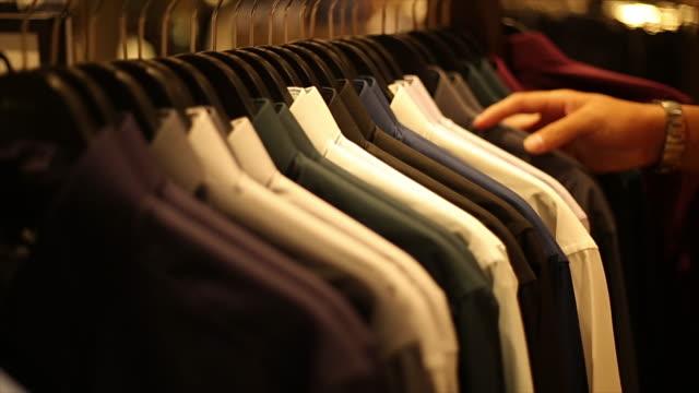 vídeos de stock, filmes e b-roll de selecionar camiseta no balcão de atendimento ao cliente - vitrine de varejo