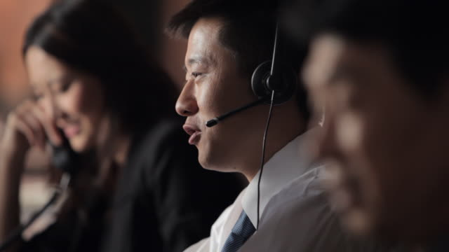 vídeos y material grabado en eventos de stock de cu selective focus customer service representatives talking in office, focus on man talking on headset / china - agente de servicio al cliente