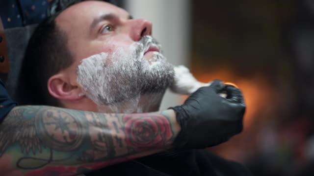 customer shaving his beard at a retro barber shop - shaving brush stock videos & royalty-free footage