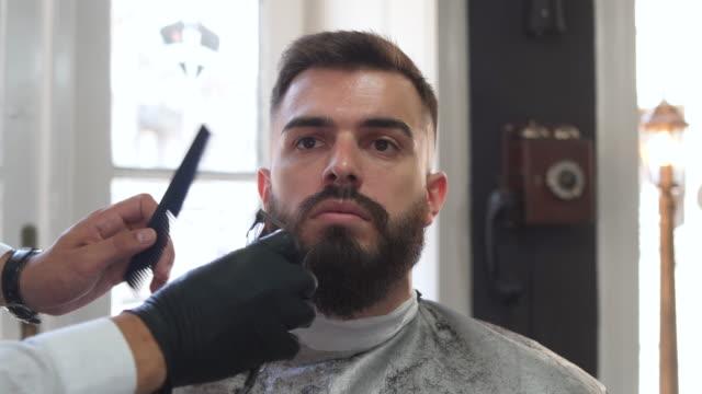customer shaving his beard at a retro barber shop - hair clipper stock videos & royalty-free footage