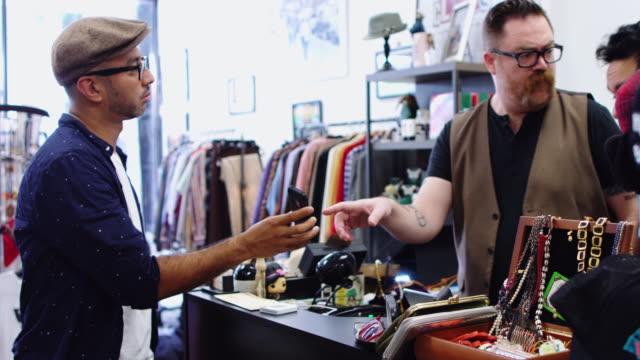 Kunden, die zeigen Bild auf Handy Einzelhandelsarbeitskraft in Vintage Store