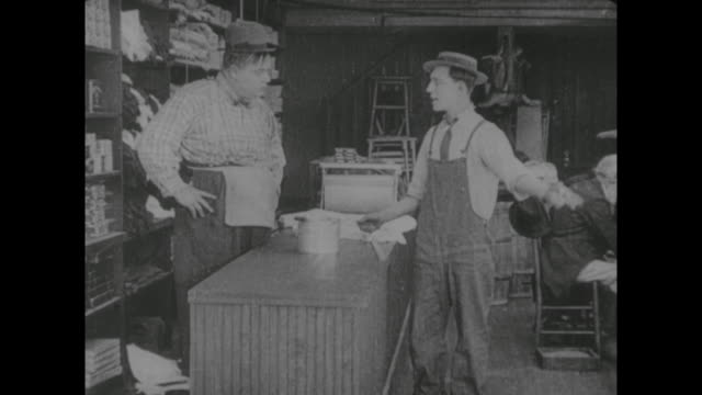 1917 customer (buster keaton) sneaks molasses syrup before taking his bucket to counter and asking clerk (fatty arbuckle) to pour some for him - fatty arbuckle stock videos and b-roll footage