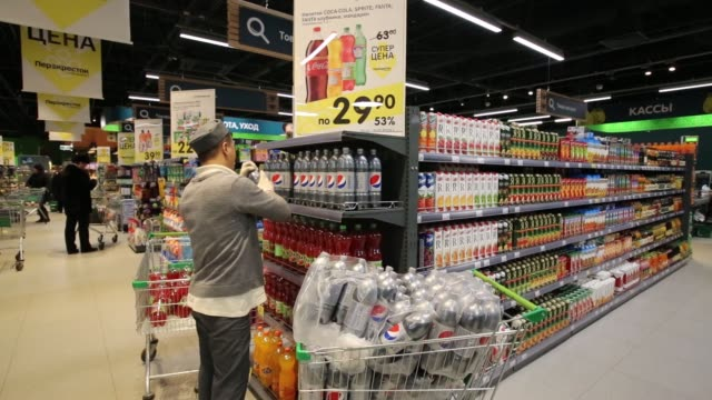 a customer stands with a shopping trolley as she looks at yogurt pots on display in the dairy area inside a perekrestok supermarket operated by x5... - cetacea stock videos & royalty-free footage