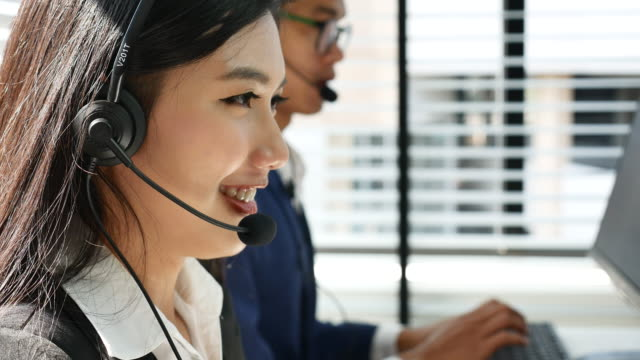 customer support operator smiling and speaking in office - call center stock videos & royalty-free footage