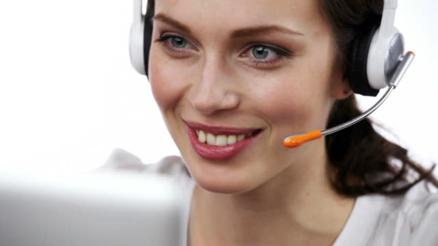 Customer support operator smiling, speaking, looking at camera, on white