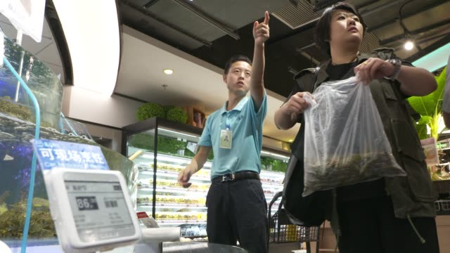 A customer takes a photograph of fish in tanks with a mobile phone in an Alibaba Group Holding Ltd Hema Store in Shanghai China on Tuesday Sept 12...