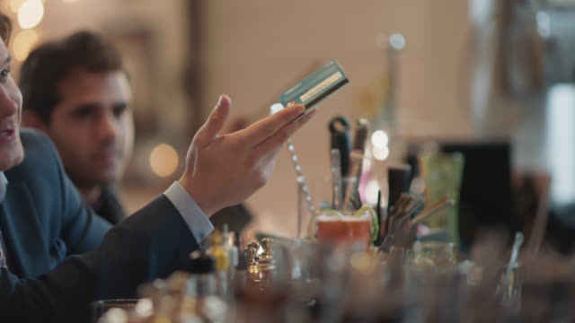 customer takes out credit card from his jacket pocket, hands it to the bartender - 20 24 år bildbanksvideor och videomaterial från bakom kulisserna