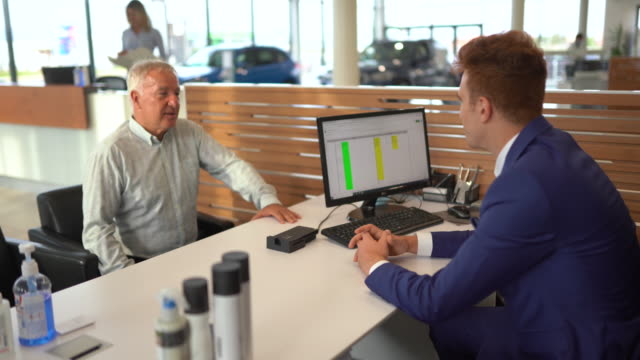 車のディーラーでマネージャーと車を購入する条件について話す顧客 - 自動車ショールーム点の映像素材/bロール