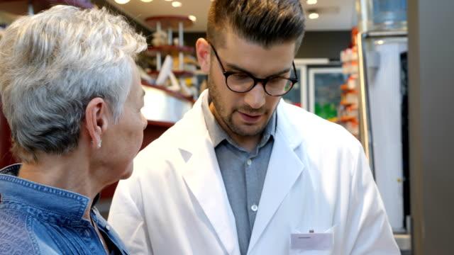kunden im gespräch mit chemiker über medizin im store - kunden orientiert stock-videos und b-roll-filmmaterial