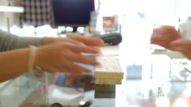 Kunden zahlen Geld für Waren mit der Frauen-Kassenführer
