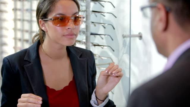 kunde versucht auf sonnenbrille in einen optiker - anpassen stock-videos und b-roll-filmmaterial